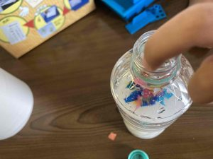 色付きの紙をペットボトルに入れる