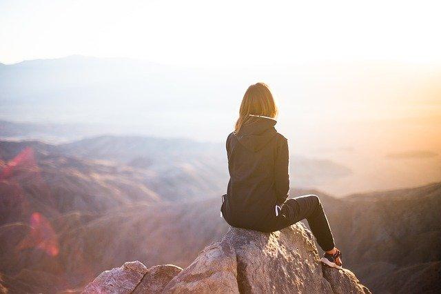 山の頂に佇む女性